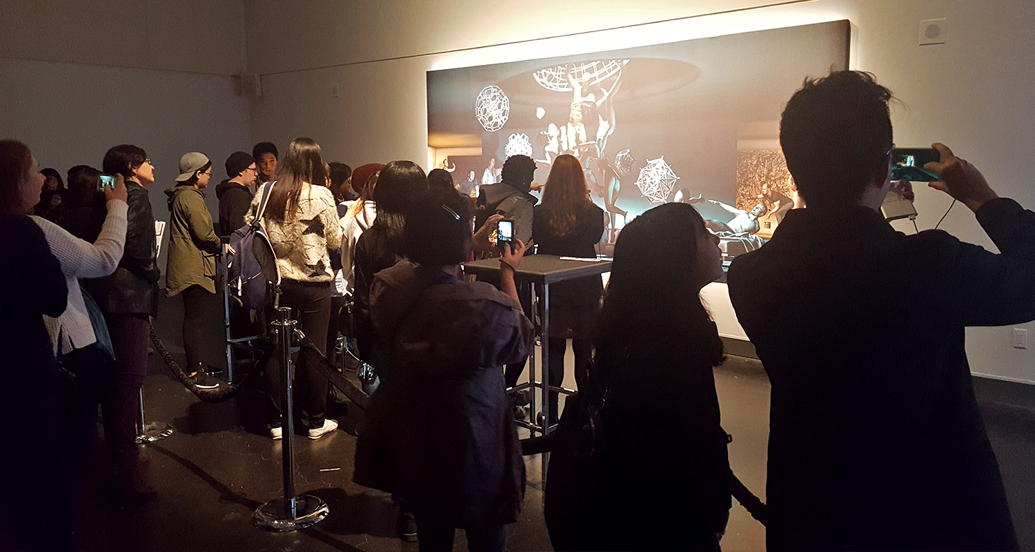 Crowd gathered around interior mural as they use the AR app.