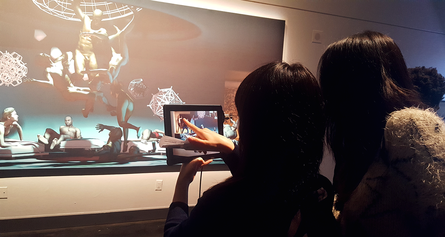 Two girls use The Merging app on a tablet to experience augmented reality.